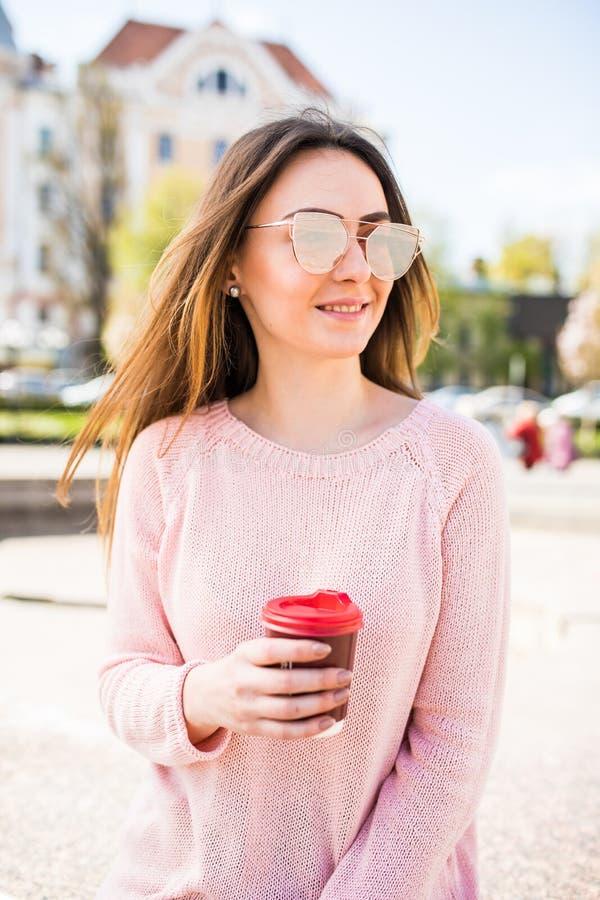 Ritratto di bella ragazza castana che cammina giù la via che tiene bevanda asportabile in un sorridere della mano Scena urbana de fotografia stock