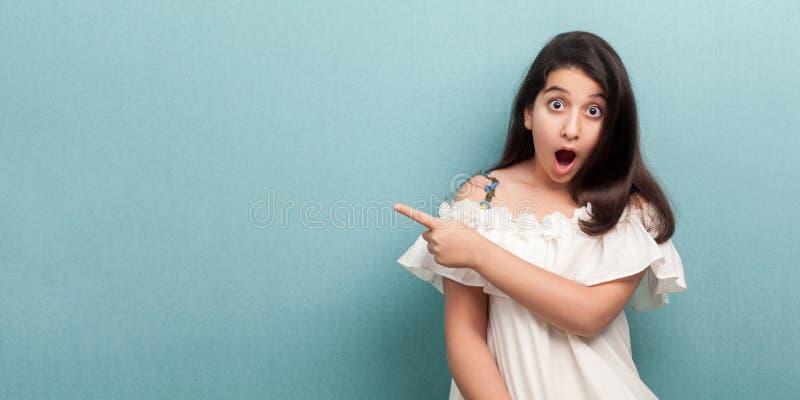 Ritratto di bella ragazza castana con capelli diritti lunghi nella condizione bianca del vestito, indicante al copyspace vuoto de fotografia stock libera da diritti