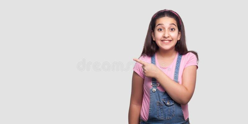 Ritratto di bella ragazza castana felice in maglietta rosa casuale e nella condizione blu dei camici, guardante con il sorriso a  immagini stock