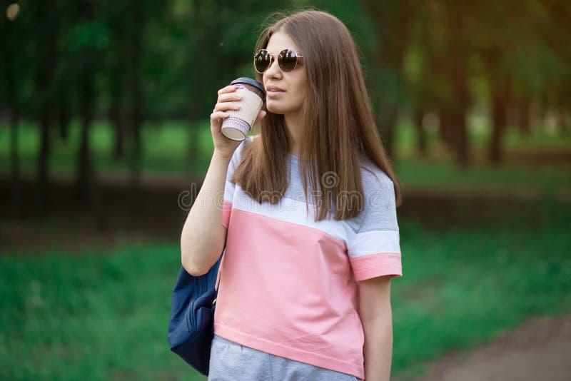 Ritratto di bella ragazza castana in occhiali da sole che cammina giù la via Tenendo bevanda asportabile a disposizione Sorridere immagine stock