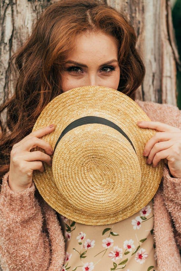 Ritratto di bella ragazza che sta vicino ad un albero estate, passeggiata in natura, ragazza dai capelli rossi in un vestito d'an immagine stock libera da diritti
