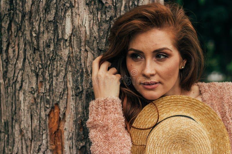Ritratto di bella ragazza che sta vicino ad un albero estate, passeggiata in natura, ragazza dai capelli rossi in un vestito d'an fotografia stock