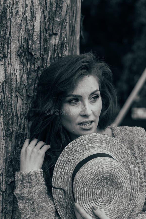Ritratto di bella ragazza che sta vicino ad un albero estate, passeggiata in natura, ragazza dai capelli rossi in un vestito d'an immagini stock