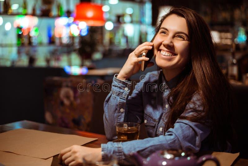 Ritratto di bella ragazza che utilizza il suo telefono cellulare nel caffè fotografie stock libere da diritti