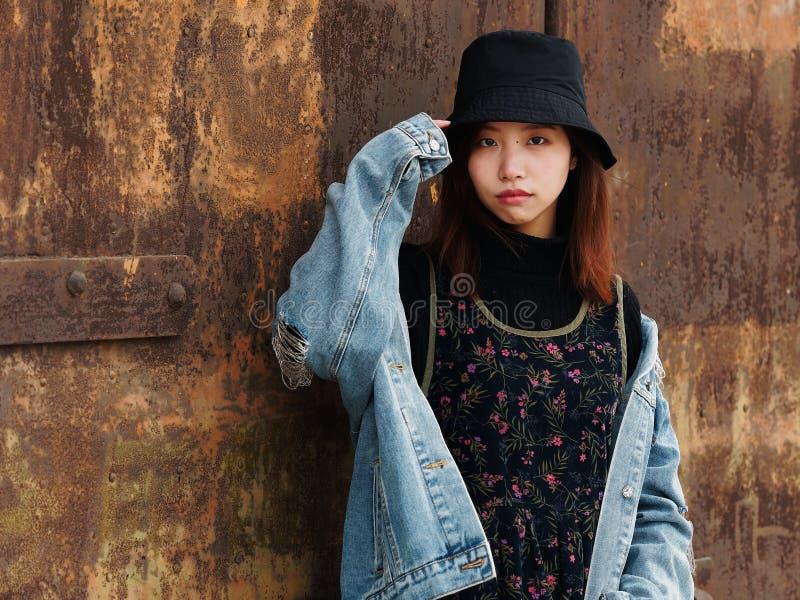 Ritratto di bella ragazza cinese in blue jeans e nella posa black hat davanti ad una porta arrugginita, ragazza sveglia immagine stock libera da diritti