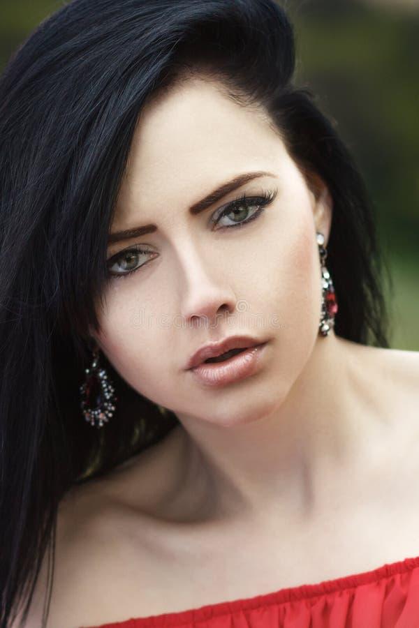 Ritratto di bella ragazza con gli occhi verdi e le spalle nude, in un vestito rosso su una natura verde di estate del fondo immagini stock libere da diritti