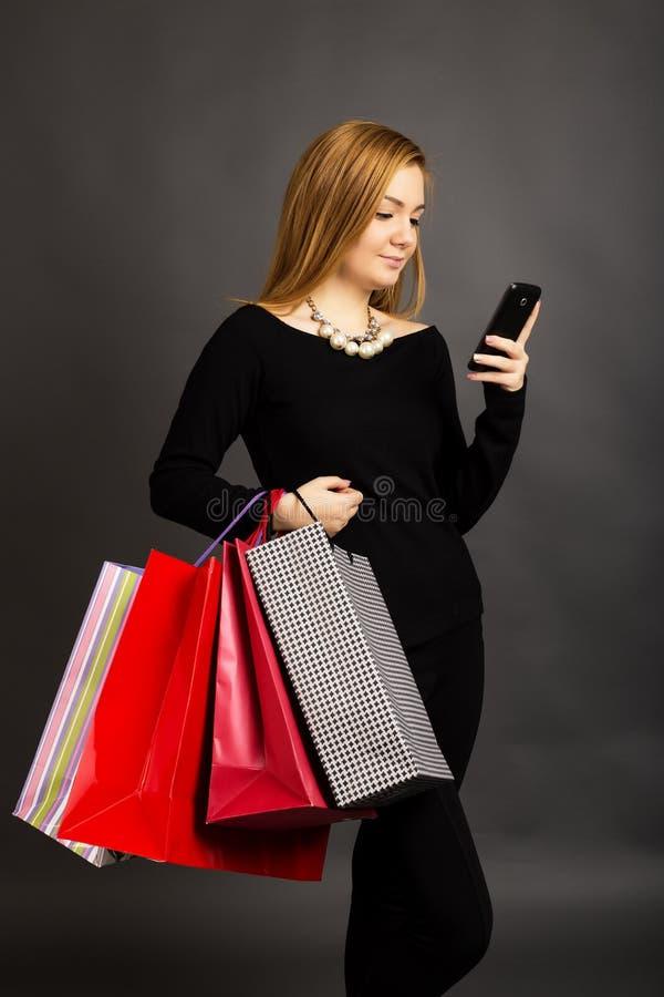 Ritratto di bella ragazza con i sacchetti della spesa che controlla i messaggi fotografia stock