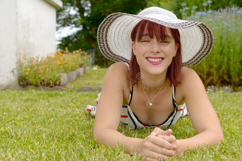Ritratto di bella ragazza con il cappello di estate, trovantesi sull'erba immagini stock libere da diritti