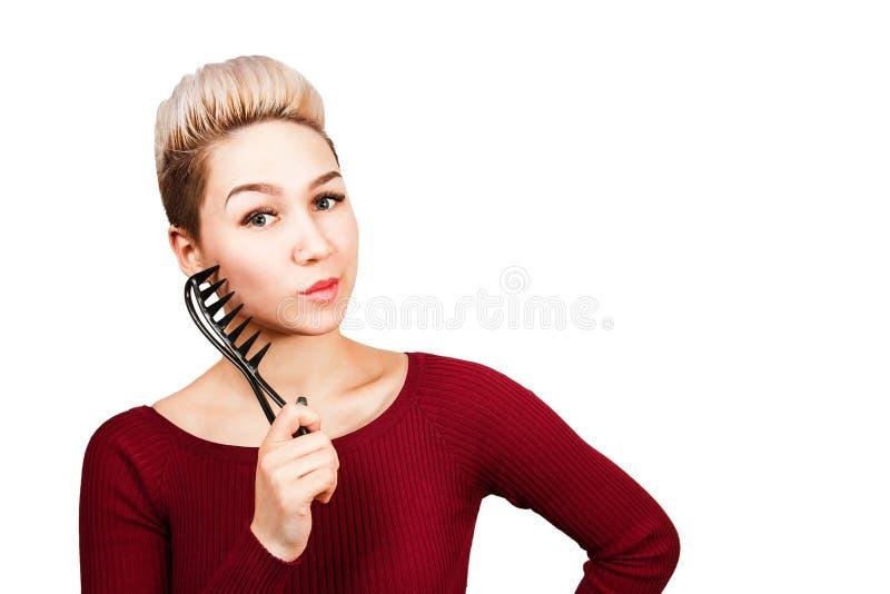 Ritratto di bella ragazza con il pettine moderno della tenuta dell'acconciatura Isolato su priorit? bassa bianca fotografia stock