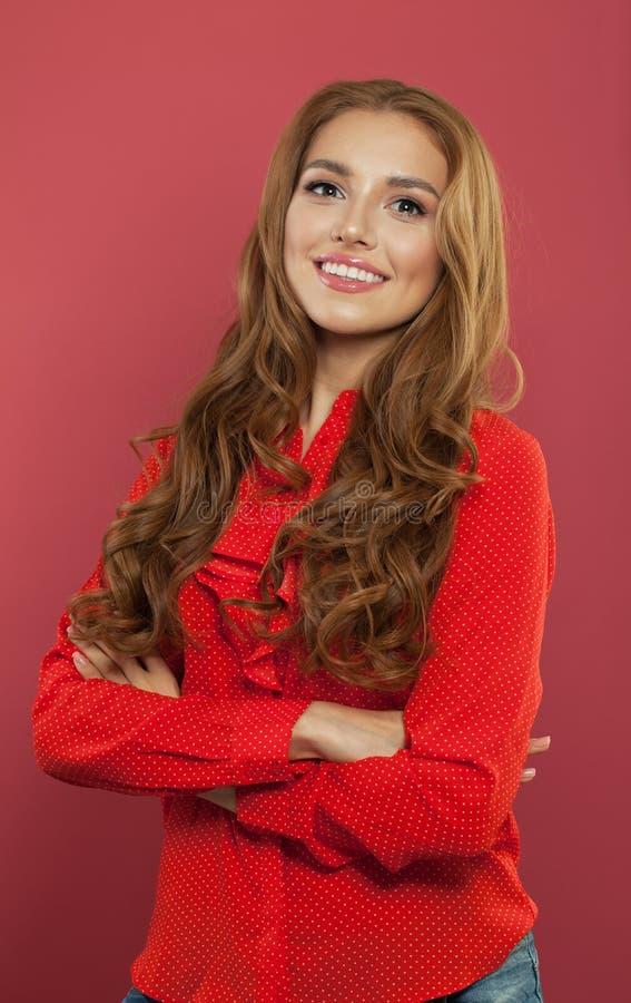 Ritratto di bella ragazza con le armi attraversate ed il sorriso sveglio Giovane donna felice sopra fondo rosa variopinto fotografia stock