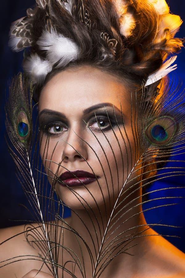 Ritratto di bella ragazza con le piume nella sua acconciatura immagini stock libere da diritti
