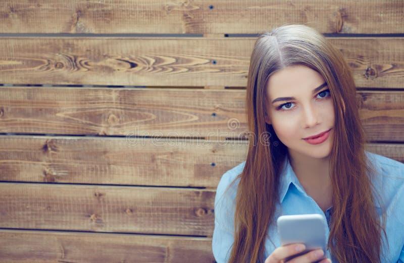 Ritratto di bella ragazza con lo Smart Phone in mani che si siedono sui precedenti della parete dei bordi di legno fotografia stock