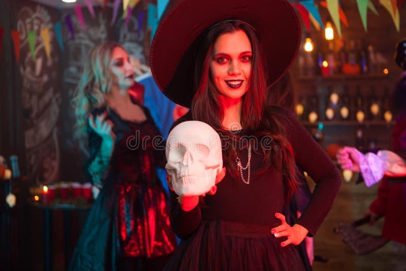 Ritratto di bella ragazza con un grande cappello agghindato come una strega per la celebrazione di Halloween immagine stock libera da diritti