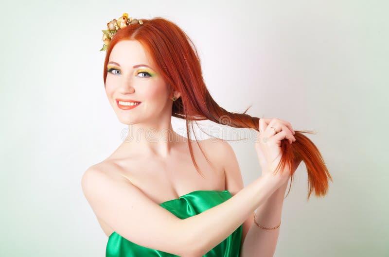 Ritratto di bella ragazza dai capelli rossi con i fiori in capelli immagine stock