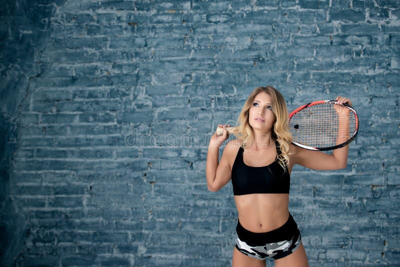 Ritratto di bella ragazza della ragazza con una racchetta, un fondo grigio del muro di mattoni immagine stock libera da diritti