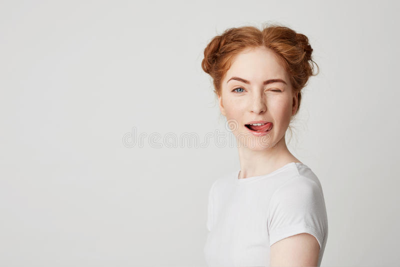 Ritratto di bella ragazza della testarossa che sorride mostrando lingua che sbatte le palpebre esaminando macchina fotografica so immagine stock