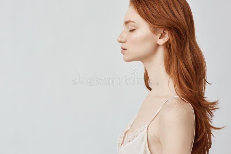 Ritratto di bella ragazza della testarossa nel profilo con gli occhi chiusi immagine stock