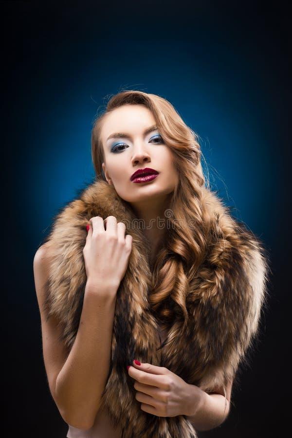 Ritratto di bella ragazza elegante che indossa un collare del procione della pelliccia fotografia stock
