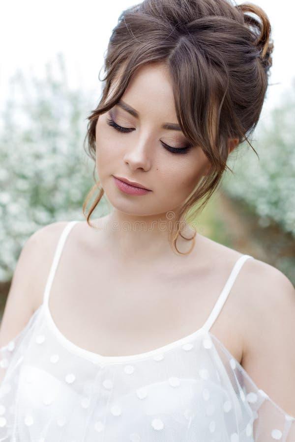 Ritratto di bella ragazza felice delicata dolce in un vestito beige con una bella acconciatura di trucco del boudoir, foto che el fotografia stock