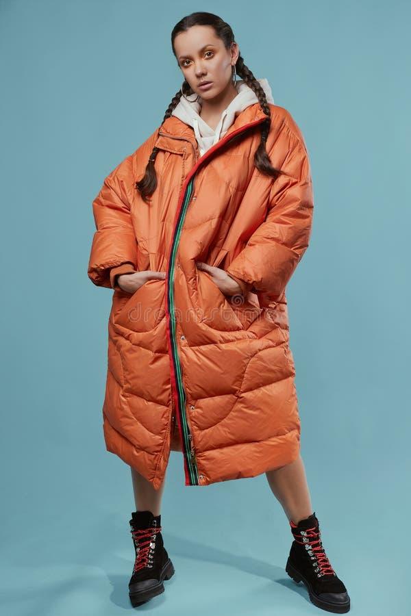Ritratto di bella ragazza ispanica affascinante in cappotto arancio lungo fotografie stock libere da diritti