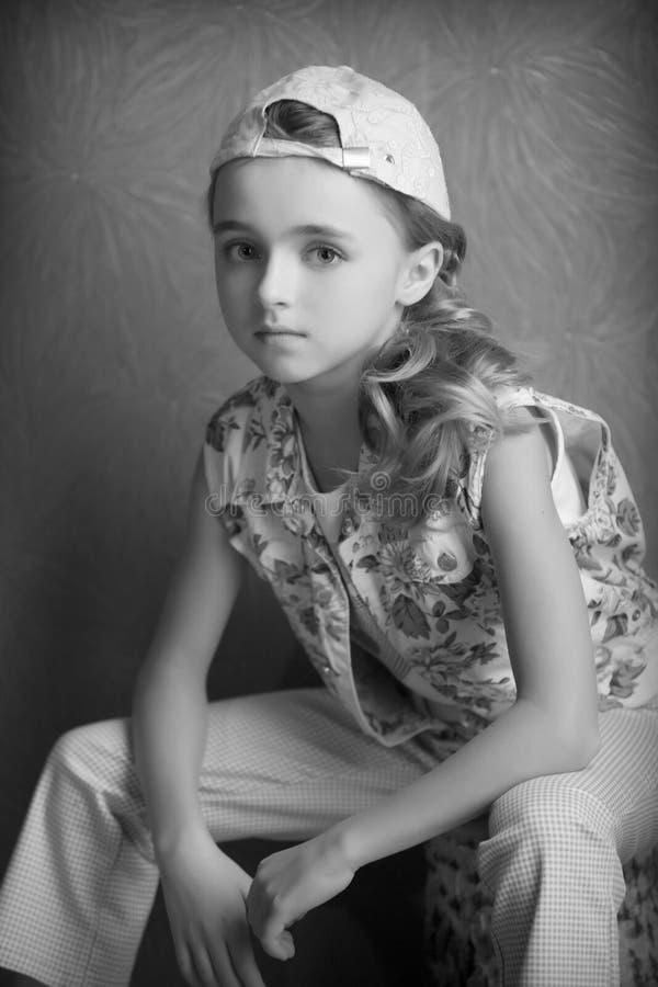 Ritratto di bella ragazza in maglietta e pantaloni nella fotografia in bianco e nero invertita della stanza del cappuccio in anti fotografia stock