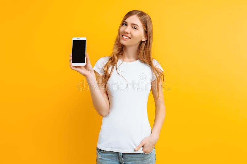 Ritratto di bella ragazza, mostrante un telefono di schermo in bianco su un fondo giallo fotografia stock libera da diritti