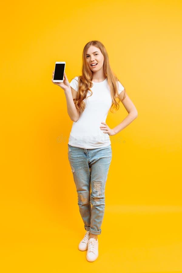 Ritratto di bella ragazza, mostrante un telefono di schermo in bianco su un fondo giallo immagini stock libere da diritti