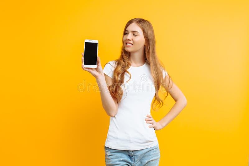 Ritratto di bella ragazza, mostrante un telefono di schermo in bianco su un fondo giallo immagine stock libera da diritti
