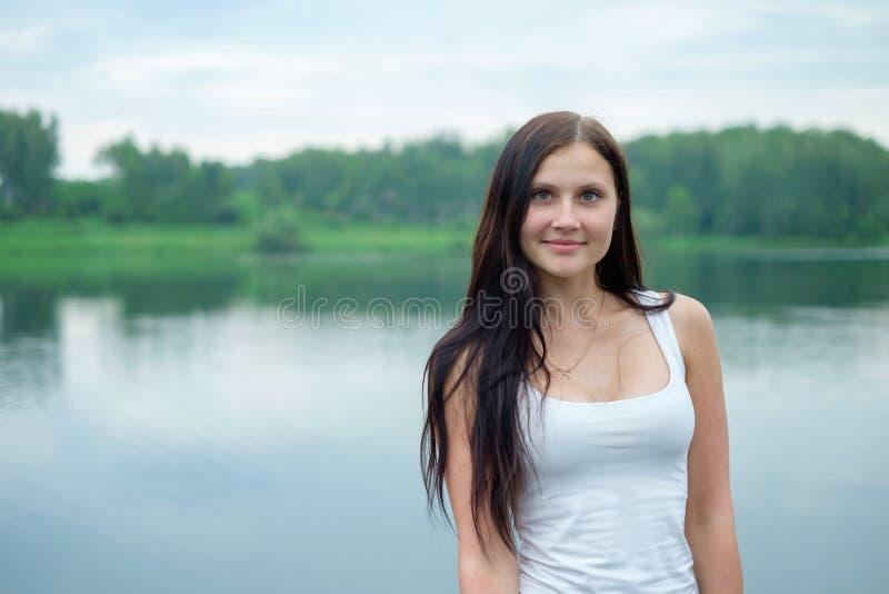 Ritratto di bella ragazza nei precedenti di un lago immagini stock libere da diritti