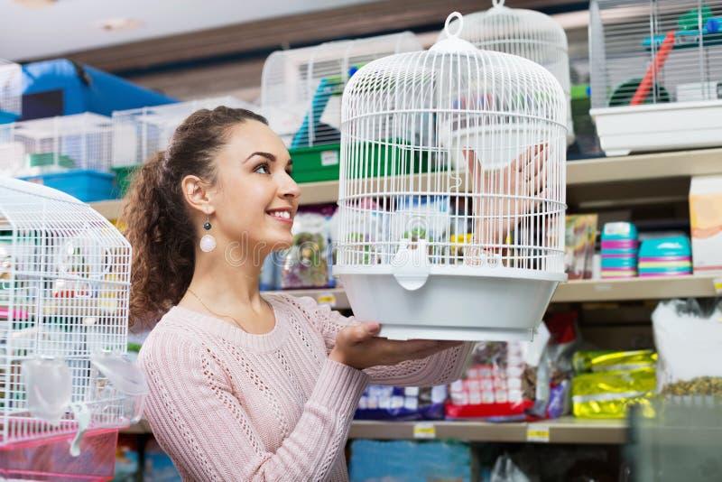 Ritratto di bella ragazza positiva che sceglie gabbia per uccelli immagini stock