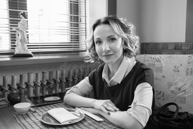 Ritratto di bella ragazza sorridente in un caffè in bianco e nero fotografia stock