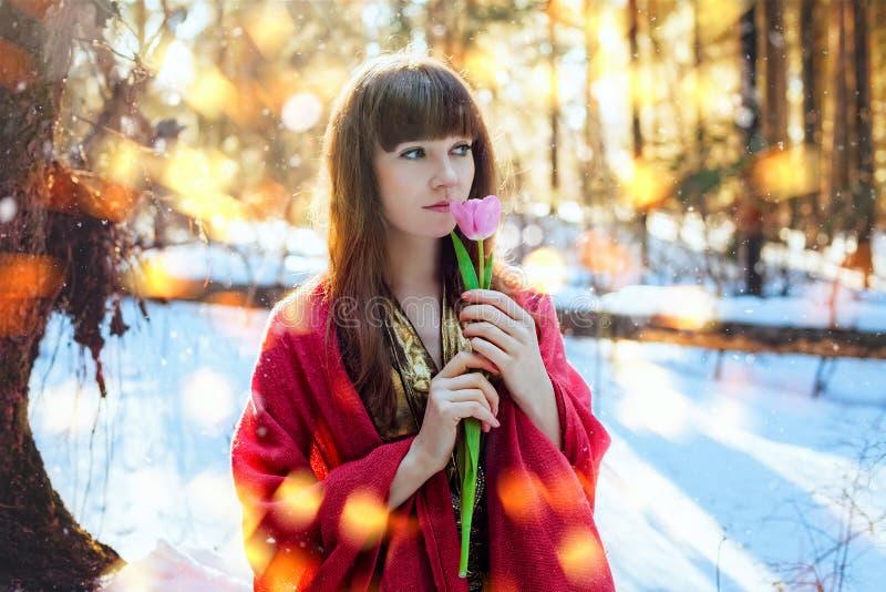 Ritratto di bella ragazza su una foresta di giorno soleggiato in primavera, che tiene un tulipano delicato Giorno soleggiato cald fotografie stock