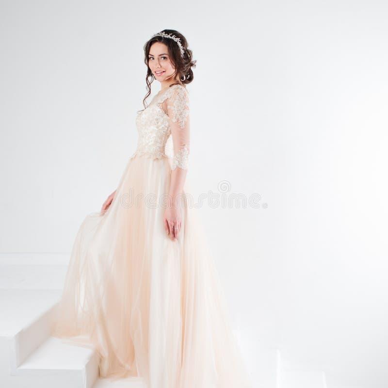 Ritratto di bella ragazza in un vestito da sposa La sposa in un vestito lussuoso che sta sulle scale, scala immagine stock libera da diritti