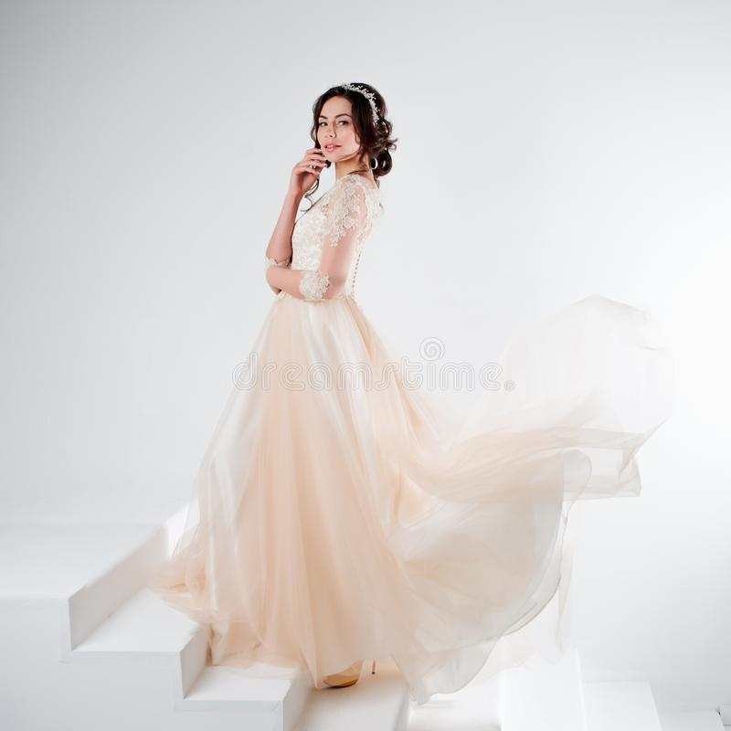 Ritratto di bella ragazza in un vestito da sposa La sposa in un vestito lussuoso che sta sulle scale, scala fotografia stock libera da diritti