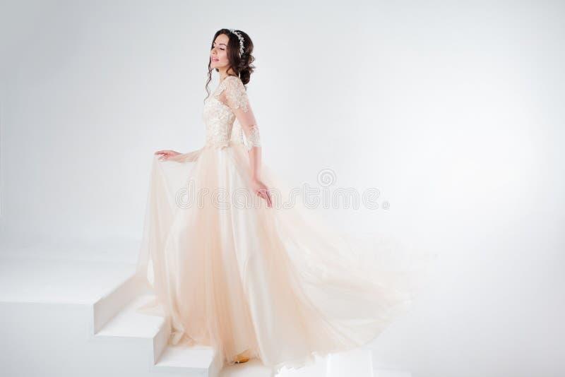 Ritratto di bella ragazza in un vestito da sposa La sposa in un vestito lussuoso che sta sulle scale, scala immagini stock