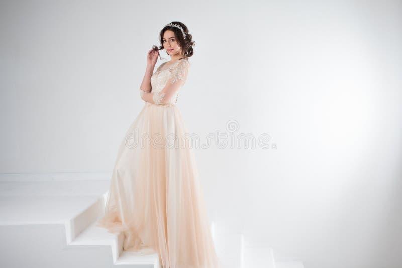 Ritratto di bella ragazza in un vestito da sposa La sposa in un vestito lussuoso che sta sulle scale, scala immagine stock