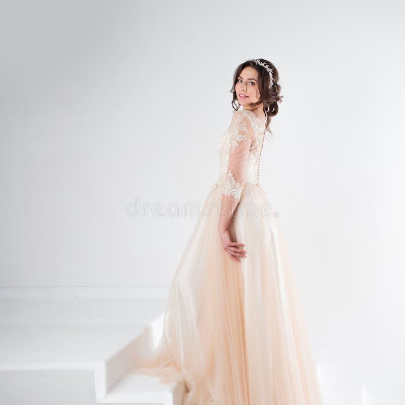 Ritratto di bella ragazza in un vestito da sposa La sposa in un vestito lussuoso che sta sulle scale, scala fotografie stock libere da diritti