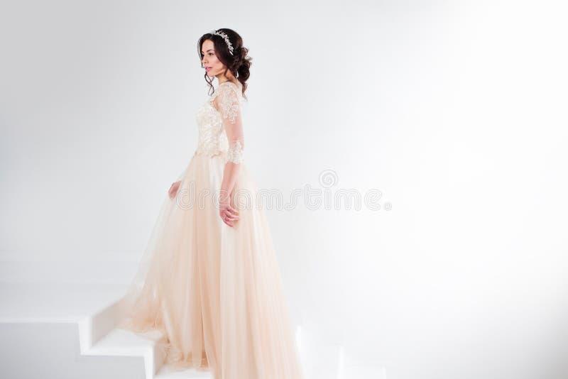Ritratto di bella ragazza in un vestito da sposa La sposa in un vestito lussuoso che sta sulle scale, scala fotografia stock