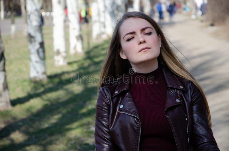 Ritratto di bella ragazza in un vestito rosso scuro knee-deep ed in un bomber scuro nella via nei precedenti di pomeriggio immagine stock