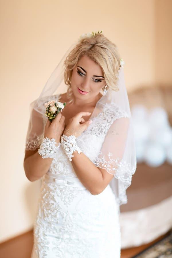 Ritratto di bella sposa bionda con l'acconciatura elegante ed il trucco che portano vestito da sposa di lusso, fuoco selettivo fotografia stock libera da diritti