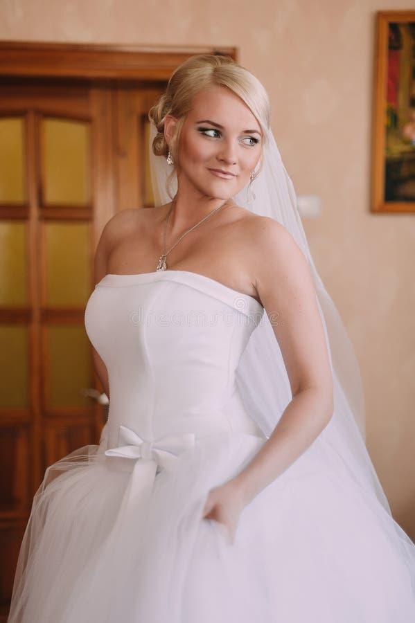 Ritratto di bella sposa con il velo di modo che posa a casa a immagini stock