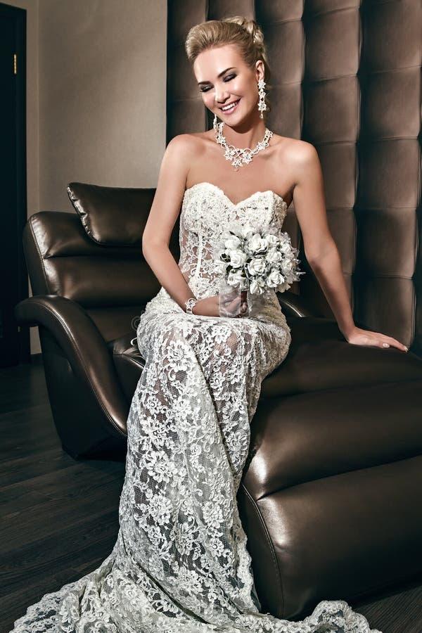 Ritratto di bella sposa felice che si siede sulla sedia e sulla tenuta immagine stock