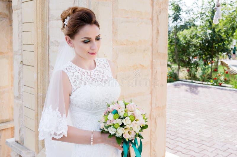 Ritratto di bella sposa in un vestito bianco e un mazzo dei fiori in sue mani immagine stock
