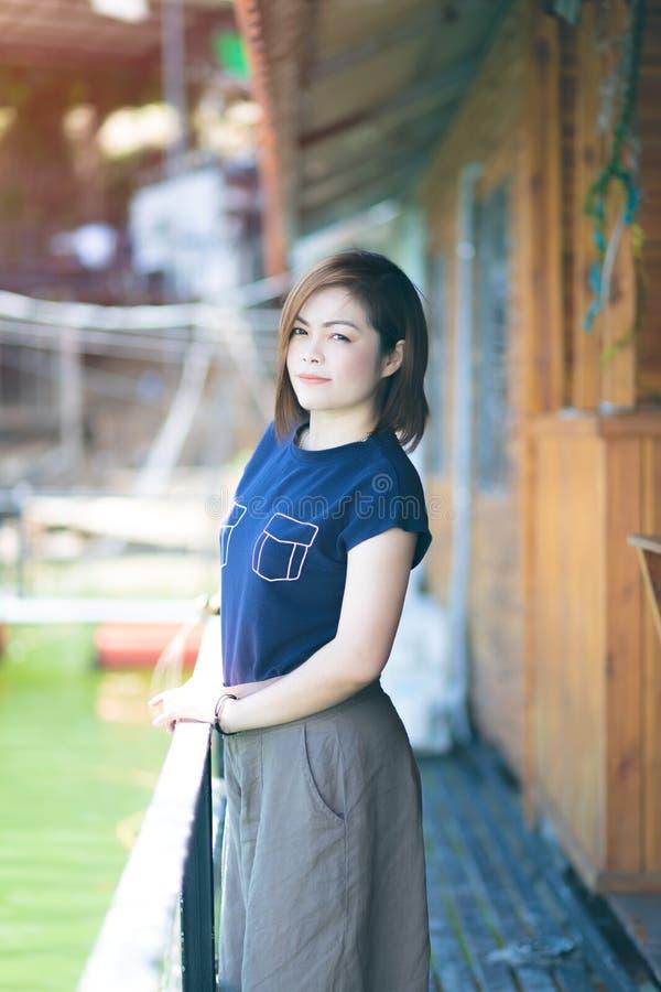 Ritratto di bella usura di donna asiatica una maglietta blu che sta brillantemente e che sorride alla macchina fotografica immagine stock