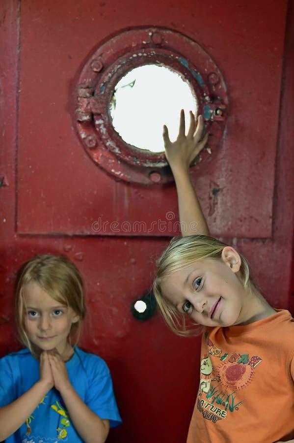 Ritratto di belle bambine sui precedenti di vecchia parete rossa del ferro con l'oblò fotografia stock libera da diritti