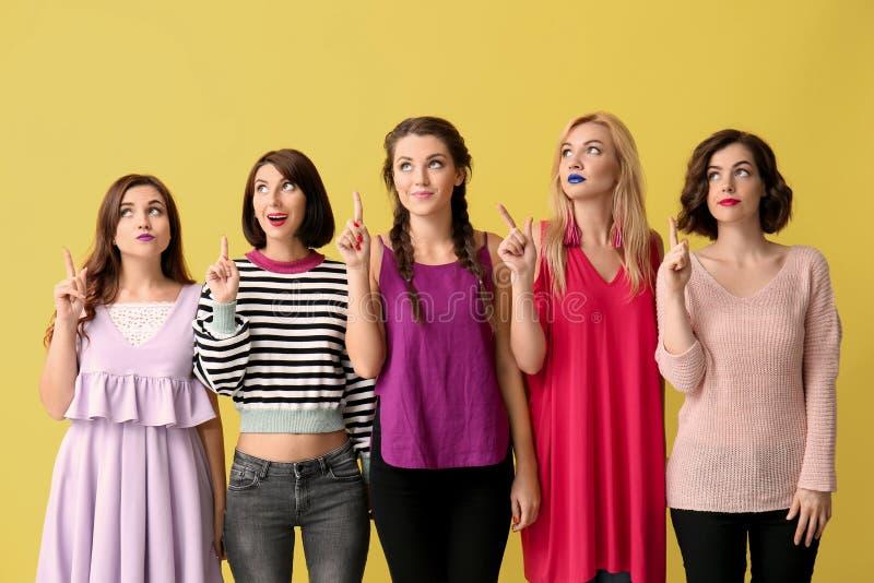 Ritratto di belle donne con i dito indice alzati sul fondo di colore fotografia stock