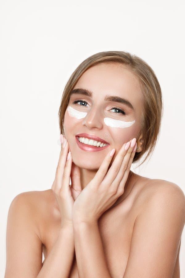 Ritratto di belle donne con pelle perfetta che applica crema sul fronte fotografia stock