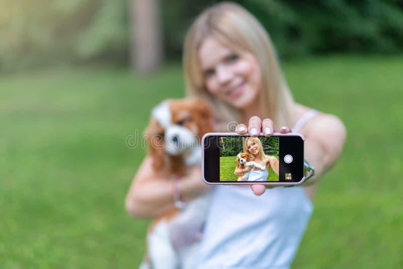 Ritratto di belle donne nel parco, abbracciante con il cane dello spaniel e facente selfie dallo smartphone immagini stock libere da diritti
