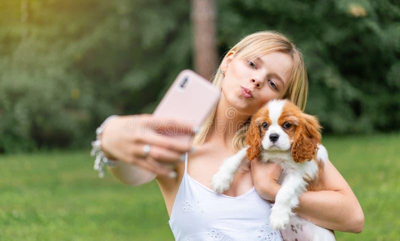 Ritratto di belle donne nel parco, abbracciante con il cane dello spaniel e facente selfie dallo smartphone fotografie stock libere da diritti