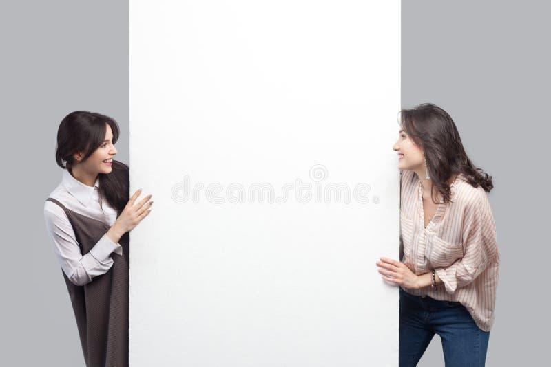 Ritratto di belle giovani donne castane felici nello stile casuale che sta vicino al copyspace in bianco bianco vuoto e che esami fotografia stock